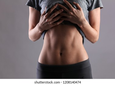 Sport, fit woman showing perfect abdomen muscles. Dieting, fitness, active lifestyle concept, copy space