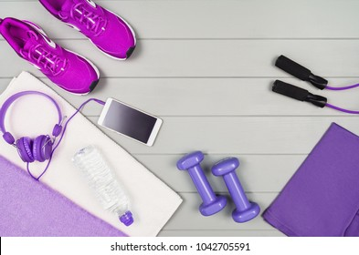 Sport and fitness accessories, healthy and active lifestyle concept on wooden floor background with copy space. Products with vibrant, punchy pastel colours. Image taken from above, top view.