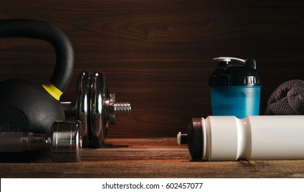 Sport fitness bodybuilding healthy lifestyle and weightlifting concept Grey towel Protein shake bottle Two Dumbbells with plates on wooden floor Gym background