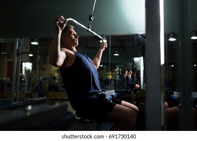 sport, fitness, bodybuilding, lifestyle and people concept - man exercising and flexing muscles on lat pull-down cable machine in gym