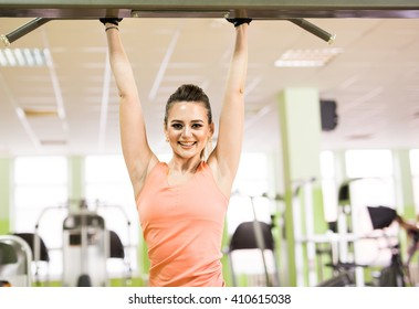 sport, fitness, bodybuilding, teamwork and people concept - young woman flexing muscles on gym machine