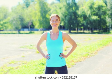 Sport, fitness concept - beautiful smiling young woman preparing to run in city park
