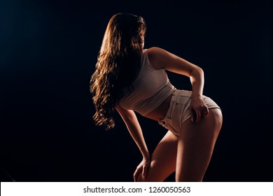 Sport, fitness and dance woman with tanned skin in sexy clothes posing on a black background in the dark. Young brunette girl with long hair dancing. Movement, twerk, healthy lifestyle, hobby concepts