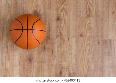 sport, fitness, game, sports equipment and objects concept - close up of basketball ball on wooden floor from top