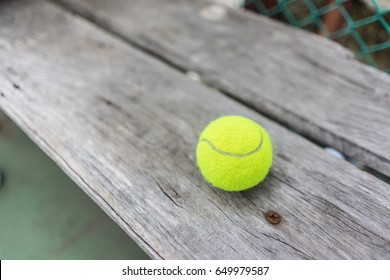 sport, fitness, game, sports equipment and objects concept - close up of tennis ball on wooden