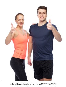 sport, fitness, gesture, lifestyle and people concept - happy sportive man and woman showing thumbs up