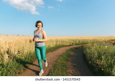 Sport, fitness, health care, cardio training. Active woman with athletic body running in the countryside. Smiling female jogger working out in the morning sunny day.