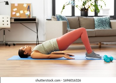 sport, fitness and healthy lifestyle concept - african american woman doing pelvic lift abdominal exercise at home