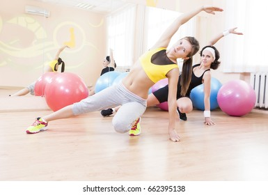 Sport, Fitness, Healthy Lifestyle Concepts.Two Female Caucasian Athletes in Good Fit Having Arms Stretching Exercises in Sport Gym.Horizontal Image