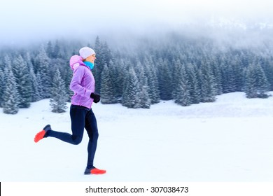 Sport, fitness inspiration and motivation. Young happy woman cross country running in mountains on snow, winter day. Female trail runner jogging exercising outdoors.