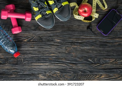 sport fitness items on dark wooden background with empty text space
