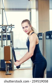 sport, fitness, lifestyle and people concept - young woman flexing muscles on gym machine.
