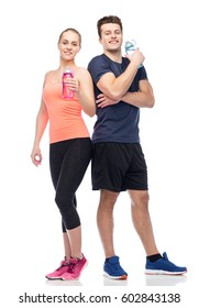 sport, fitness, lifestyle and people concept - happy sportive man and woman with water bottles