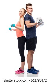 sport, fitness, lifestyle and people concept - happy sportive man and woman with dumbbells flexing muscles
