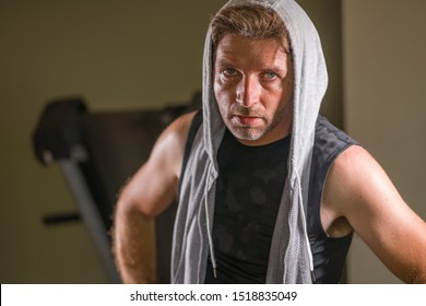 sport fitness lifestyle portrait of young tough and sweaty man exercising at gym working out sweaty in hoodie vest training boxing looking cool and badass in expressive studio light