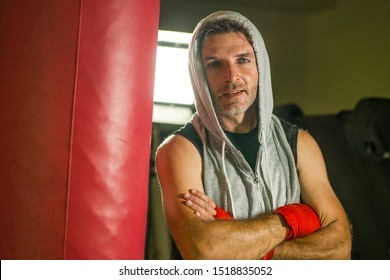 sport fitness lifestyle portrait of young happy and sweaty man boxing at gym working out sweaty in hoodie vest training on heavy bag looking cool in expressive studio light