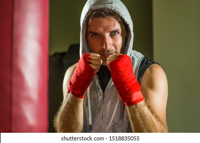 sport fitness lifestyle portrait of young happy and sweaty man boxing at gym working out sweaty in hoodie vest training on heavy bag looking cool and badass in expressive studio light