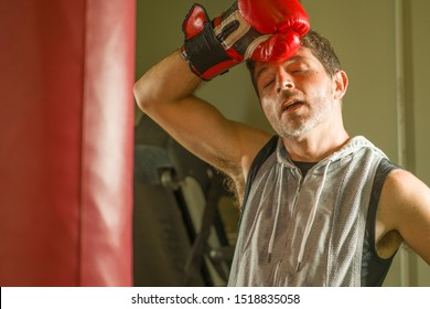 sport fitness lifestyle portrait of young tough and sweaty man boxing at gym working out sweaty and tired in hoodie vest exhausted after training on heavy bag in boxer gloves