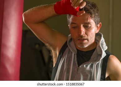 sport fitness lifestyle portrait of young tough and sweaty man boxing at gym working out sweaty and tired in hoodie vest exhausted after training on heavy bag in fighter wrist wraps