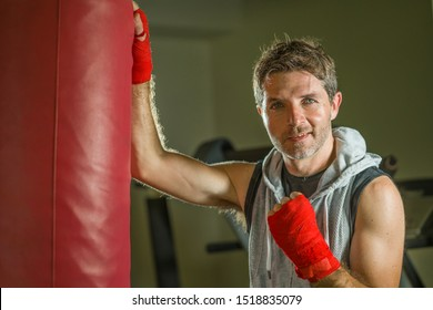 sport fitness lifestyle portrait of young happy and sweaty man boxing at gym working out sweaty in hoodie vest training boxing on heavy bag looking cool smiling positive in fighter wrist wraps