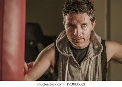 sport fitness lifestyle portrait of young tough and sweaty man boxing at gym working out sweaty in hoodie vest training on heavy bag looking cool and badass in expressive studio light