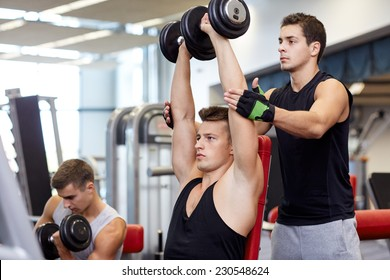 sport, fitness, lifestyle, powerlifting and people concept - group of men with dumbbells and personal trainer flexing muscles in gym