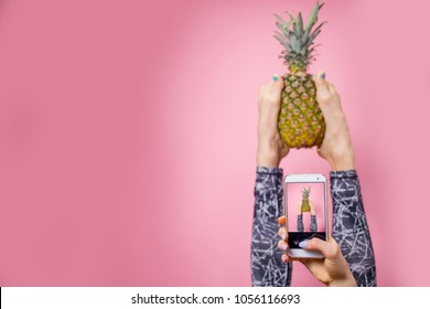 Sport, fitness, lifestyle, technology and people concept - young woman with smartphone taking selfie in gym while holding pineapple with her legs over pink background