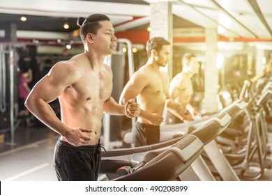 Sport, fitness, lifestyle, technology and people concept - smiling asian men exercising on treadmill in gym