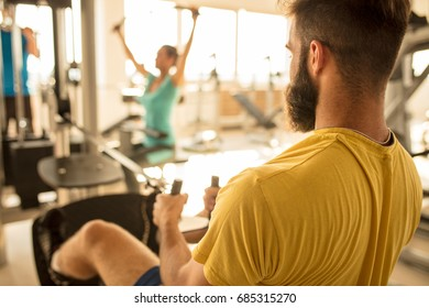 Sport, fitness, lifestyle, technology and people concept. Young man training in the gym