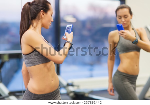 sport, fitness, lifestyle, technology and people concept - young woman with smartphone taking mirror selfie in gym