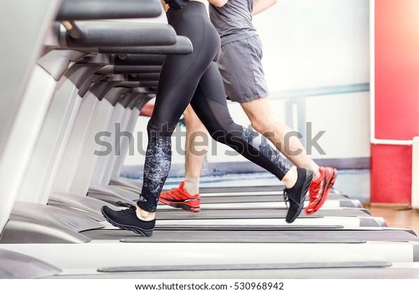 Deporte, fitness, estilo de vida, tecnología y concepto de la gente - cerca de las piernas de hombres y mujeres caminando en los carriles en el gimnasio.