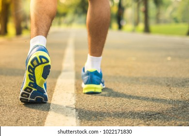 Sport fitness man legs walking in the park outdoor, runner running on the road outside, young athlete jogging and exercise on footpath in sunlight morning. Sport, healthcare and well being concepts