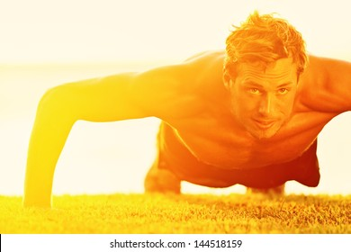Sport fitness man push-ups. Male athlete exercising push up outside in sunny sunshine. Fit shirtless male fitness model in crossfit exercise outdoors. Healthy lifestyle concept.