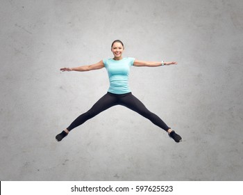 sport, fitness, motion and people concept - happy smiling young woman jumping in air over gray concrete wall background