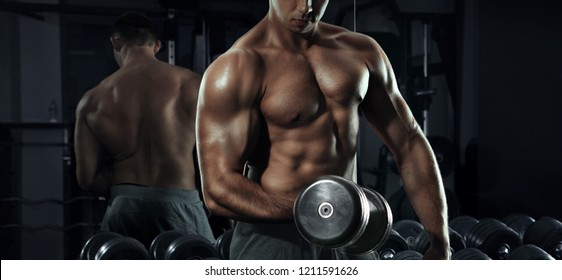 Sport and fitness. Muscular bodybuilder in the gym training with dumbbells.