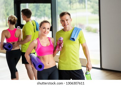 sport, fitness and people concept - smiling couple with water bottles, exercise mat and towel in gym