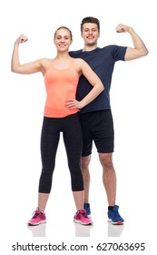 sport, fitness, power, strength and people concept - happy sportive man and woman showing biceps