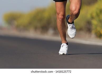 Sport and fitness runner man running on road training for marathon run doing high intensity interval training sprint