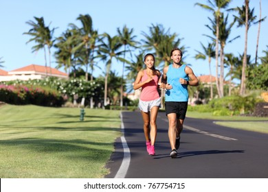 Sport fitness runners couple running lifestyle. Healthy people jogging together in summer city street outdoor, athletes training cardio in residential neighborhood.