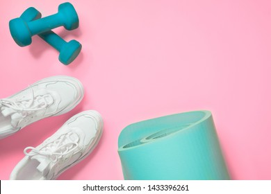 Sport and fitness shoes, dumbbell, yoga mat on pink. Space for text. Flat lay, top view minimal background.