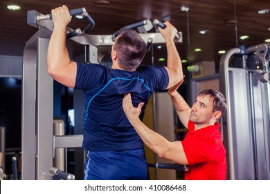sport, fitness, teamwork, bodybuilding people concept - man and personal trainer.