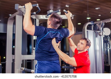 sport, fitness, teamwork, bodybuilding people concept - man and personal trainer with barbell weight lifting group weightlifting workout exercise gym.