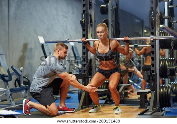 Sport-, Fitness-, Teamwork-, Körper- und Personenkomplex - junge Frau und Personal Trainer mit Barbell-Muskeln im Fitnessraum