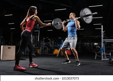 Sport, fitness, teamwork and couple concept. Female personal trainer motivating athlete training with barbell in a gym.