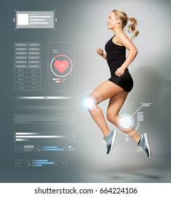 sport, fitness and technology concept - young woman in black sportswear jumping in gym