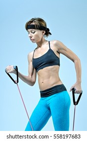 Sport fitness woman doing workout exercise with stretching expander on light-blue background. Studio shoot.