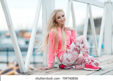 Sport fitness woman in pink sportswear outdoors doing yoga stretching and fitness exercise near the sea. Healthy lifestyle - fit sporty girl at workout training outdoor in autumn at ocean.