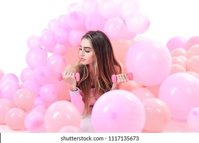 Sport, fitness, workout. Beauty, fashion. Holidays, celebration, lifestyle concept. Beautiful model girl lying in pink balloons with dumbbells. Girl with perfect makeup.Fashion woman with air balloons