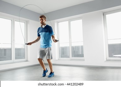 Sport And Fitness Workout. Healthy Athletic Man With Muscular Body In Fashion Headphones, Sportswear Skipping With Jump Rope, Exercising Indoor. Handsome Male Doing Jumping Cardio Exercise Training.