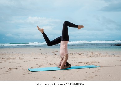 sport, fitness, yoga, people and health concept - young woman doing headstand exercise on beach background